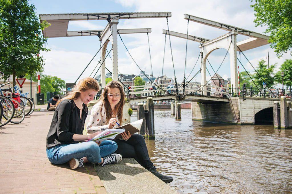 Två tjejer studerar vid bro