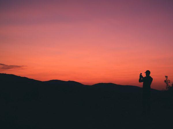 Person fotograferar solnedgång