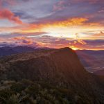 Solnedgång bland vulkan topparna i Auckland