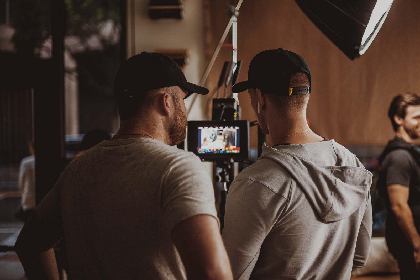 Två killar om står vid en kamera