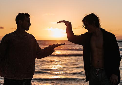 Två vänner high fivear varandra i solnedgången